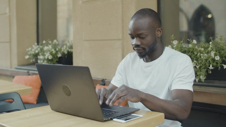 Man working remotely from a coffee shop