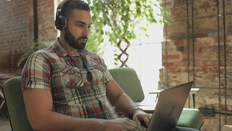Man works on laptop with headphones in coworking space