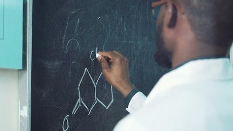 Man writing a chemical formula on the blackboard