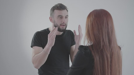Man yells at woman and gestures angrily on white background