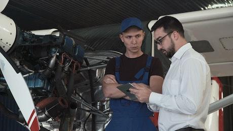Manager talking to plane mechanic