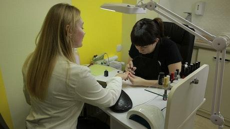 Manicurist applying nail polish