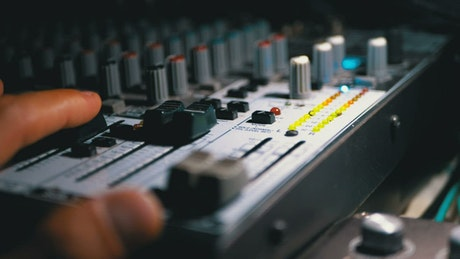 Man's hand working on a sound mixing console