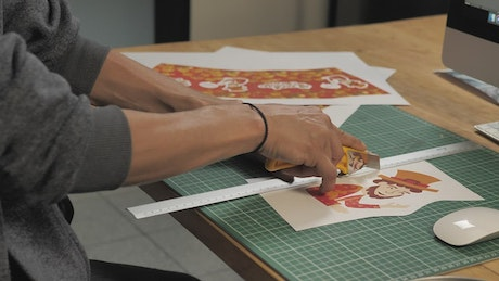 Man's hands cut a printed illustration with a cutter