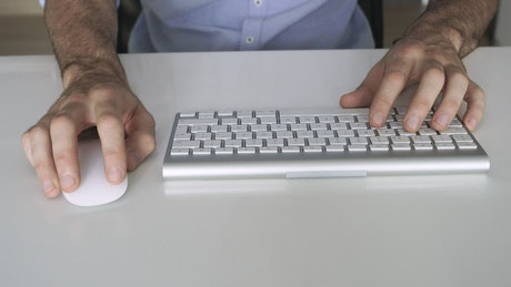 Man's hands typing on a keyboard