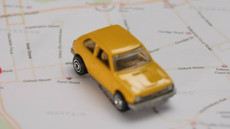 Map of a city with a toy car and pushpins