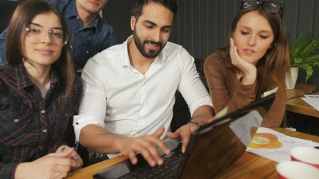 Marketing team gather around laptop and smile at camera