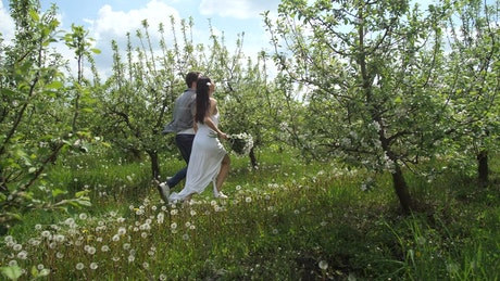 Married couple running through trees
