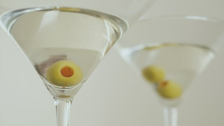 Martini glasses with olives on a white background