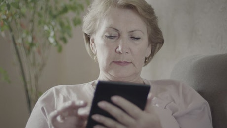 Mature woman using an electronic reading device
