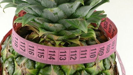 Measuring tape rounding a pineapple