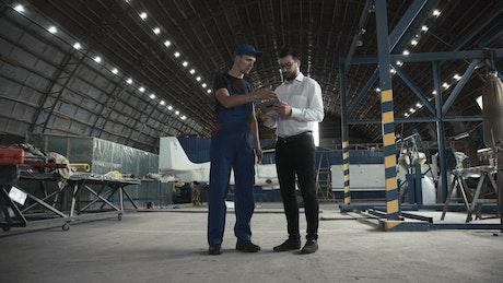 Mechanic and engineer walking in the hangar