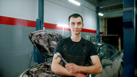 Mechanic holding a repair tool with a broken car in the background
