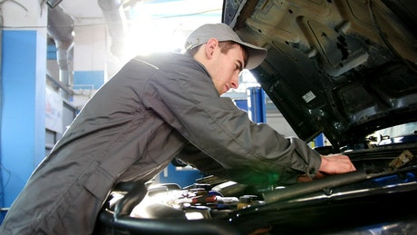 Mechanic in overalls working under the hood of a car
