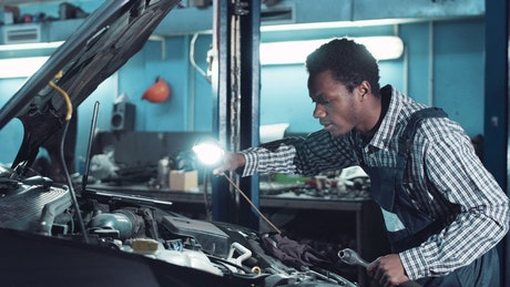 Mechanic inspecting motor with a light