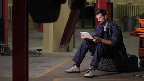 Mechanic using a tablet in a workshop