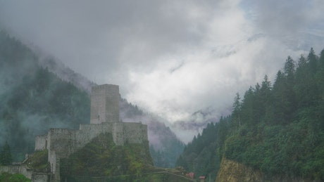 Medieval castle in a cloudy forest