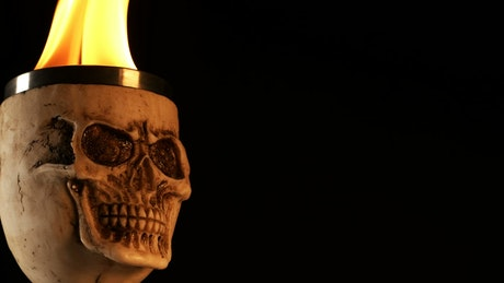 Medieval skull-shaped mug with fire in it