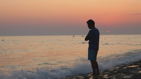 Meditative man on the shore of a beach at sunset
