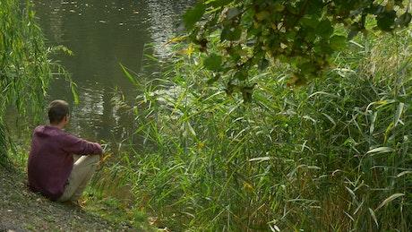 Meditative man sitting on the shore of a lake
