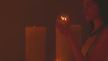 Meditative woman appreciating a small candle