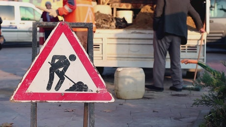 Men cleaning a street with a dirt road signs