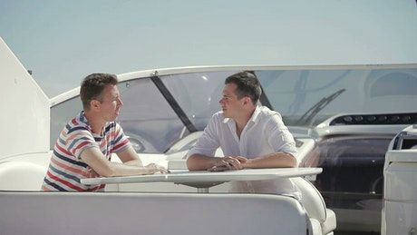 Men discuss business sale on deck of yacht