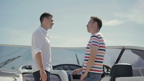 Men handshake over deal on deck of yacht