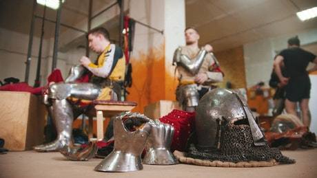 Men in the dressing room taking off the armor