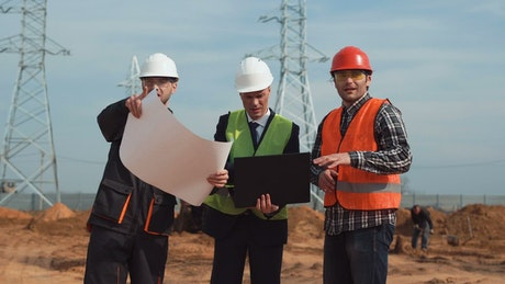 Men on constructions site checking the blueprint