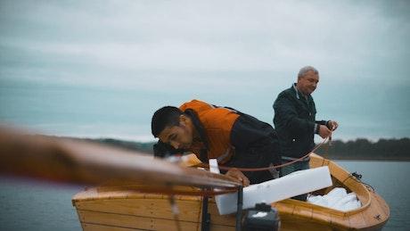 Men placing the mast of a sailboat
