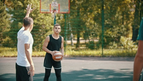 Men playing basketball on an outdoor court