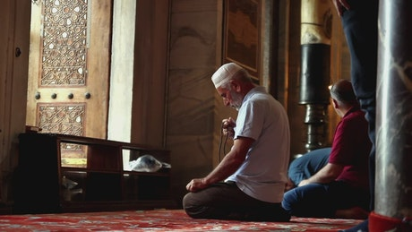 Men praying inside a mosque on the floor