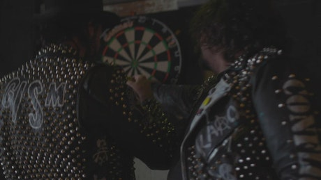 Men remove darts from a board