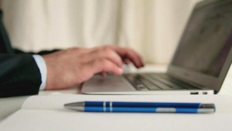 Men taking note while browsing in a laptop