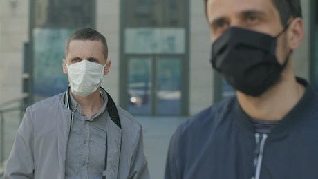 Men wearing face masks and social distancing