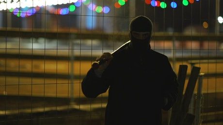Menacing man with a baseball bat at night