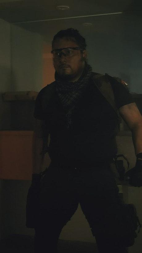 Mercenary draws his gun in an abandoned hospital