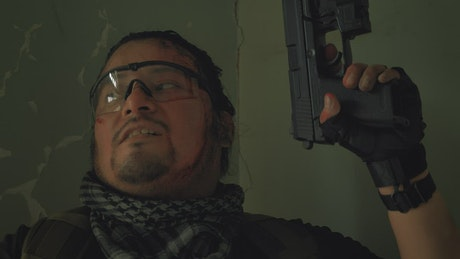 Mercenary with a gun in an abandoned place