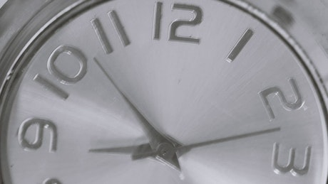 Metal analog clock moving fast in a close up shot
