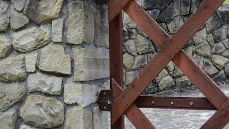 Metal gate against a stone wall