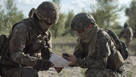 Military men looking at cell phone and map