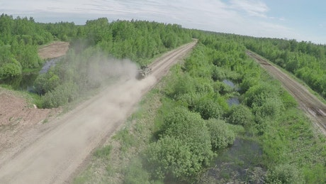 Military vehicle heading down a dusty road