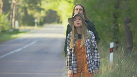 Millennial couple hitchhiking on forest road