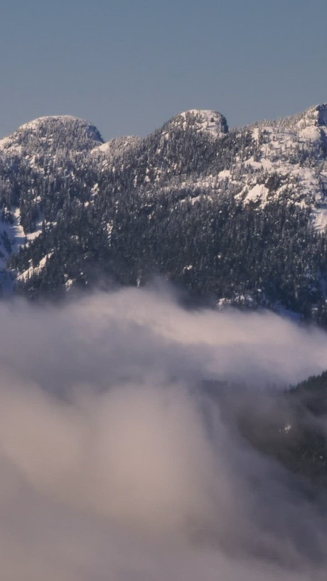 Mist at the base of a snowy mountain
