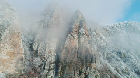 Mist covering a snow topped mountain