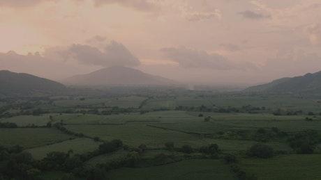 Misty sunrise over green fields