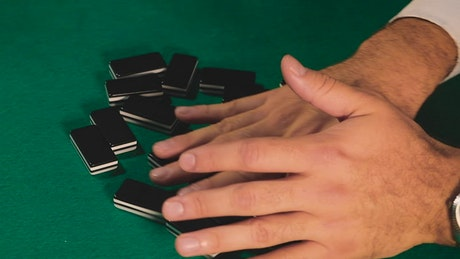 Mixing dominoes on a gaming table