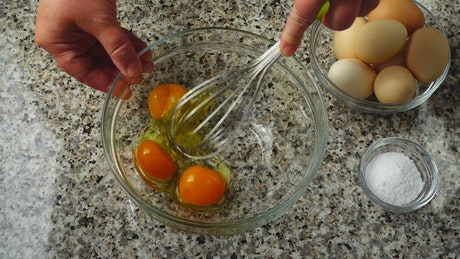 Mixing eggs in a glass bowl