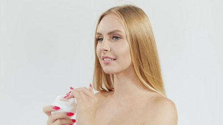 Model applies skincare cream to face on white background